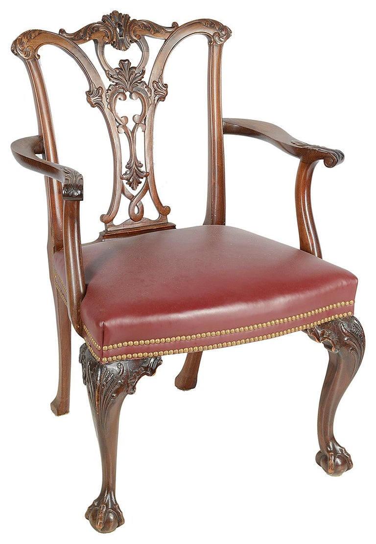 A good quality set of twelve (10 + 2 arms) late 19th century mahogany Chippendale style mahogany dining chairs, each having wonderful carved and fretted back splats of scrolls and foliage. Burgundy colour hide upholstered seats with two lines of