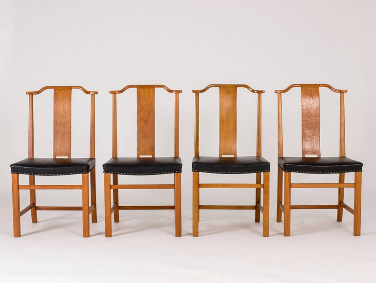 Set of 12 beautiful dining chairs in stained elmwood and leather by Axel Larsson, custom-made for a Swedish Court of Appeals. Dignified design with tall backs, discreet curves and a stable base.