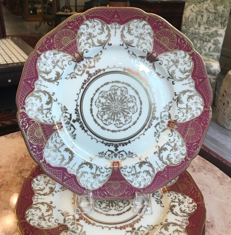 An elegant set of 12 gilt decorated service dinner plates by Black Knight, early 20th century. Unusual red clay color background with elaborate gilt overlay detail with centre medallion. Centre lacy medallion with circular gold bands around. Price