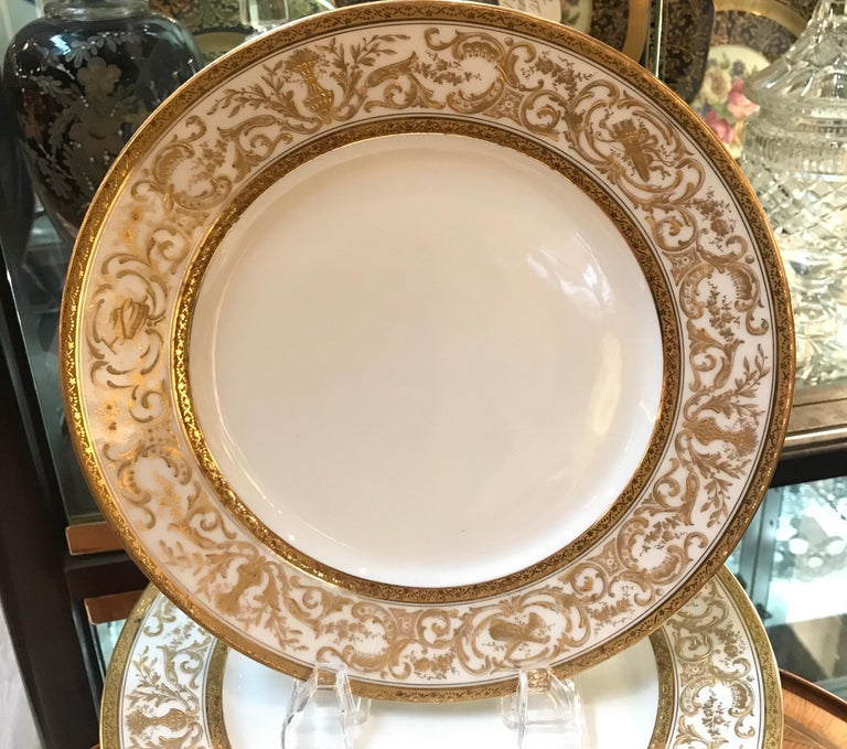 A set of elegant French porcelain raised gilt 9.75 inch dinner plates. The smaller dinner plates are the classic size from circa 1900 with a white porcelain body with delicate and lacey hand applied raised gilt decoration. The plates were retailed