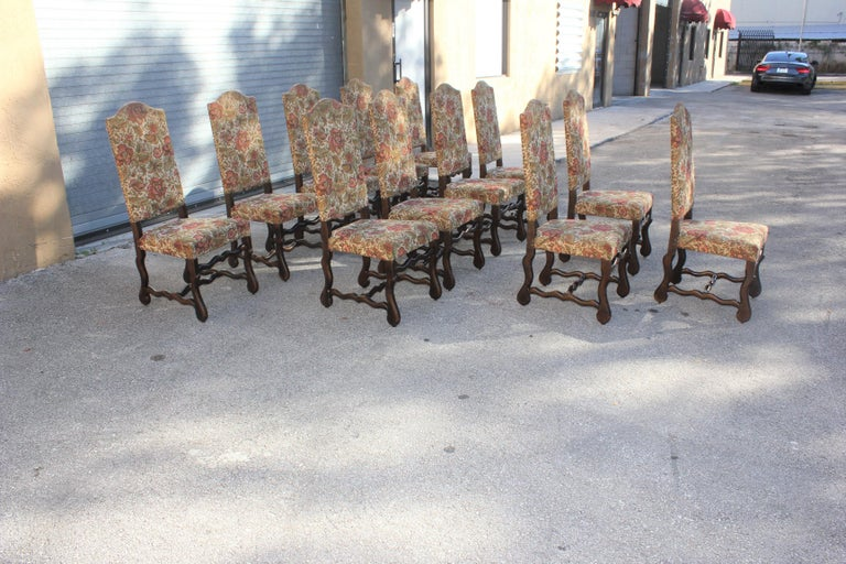 Fine set of 12 Louis XIII style Os de Mouton dining chairs with chapeau de gendarme backs, circa 1900th century. Vintage fabric upholstery with nail heads, solid walnut chair frames are in excellent condition. From South France . ( fabric