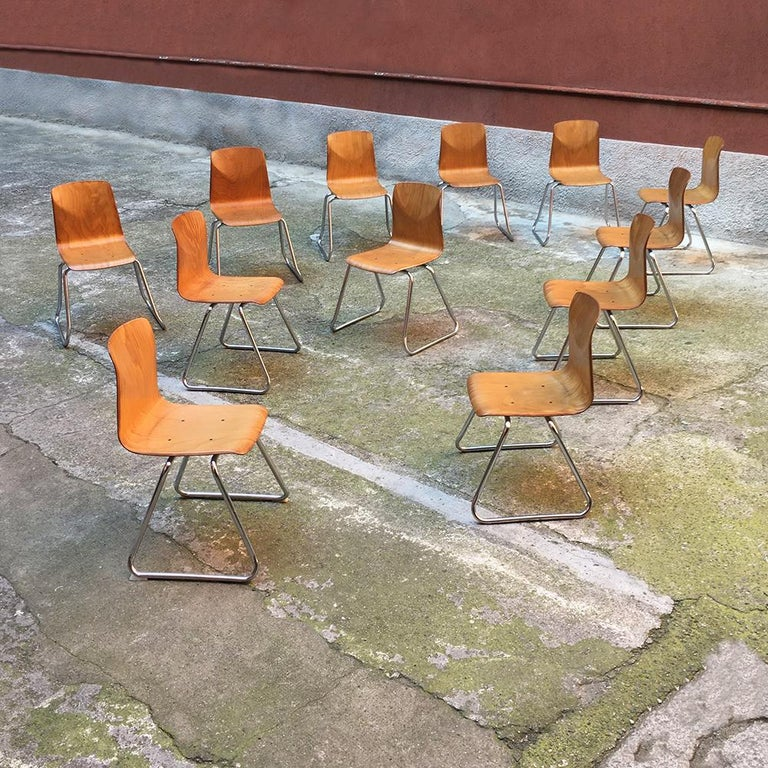 Set of 12 German vintage light wood and chromed steel Pagholz chairs, 1960s Stackable Pagholz chairs, in light wood, dating to the sixties. Basement in chromed steel and curved wooden seat Perfect condition. Measures: 55 x 42 x 77 H cm.