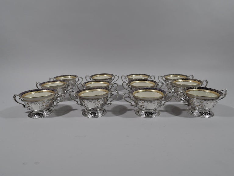 Set of 12 sterling silver bouillon bowl holders. Made by Gorham in Providence, circa 1900. Each: Curved sides with open bottom, raised spread foot, and capped high-looping double-scroll handles. Sides have chased leafing scrolls and flowers