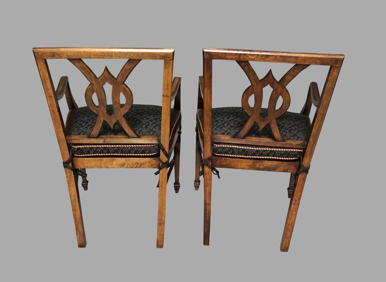 An attractive set of 12 custom designed serpentine mahogany dining chairs consisting of 10 side and 2 arm chairs in the neoclassical taste, each chair with an interlaced splat framed by straight stiles resting on square tapered legs, joined by