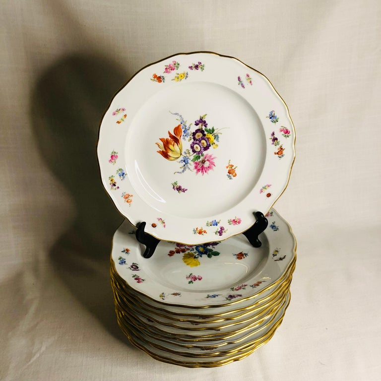 This is a fabulous set of twelve Meissen dinner plates. Each of these Meissen dinner plates are beautifully painted with a different large central flower bouquet. The artwork on these plates is exceptional. Inside the gold border, you. can see