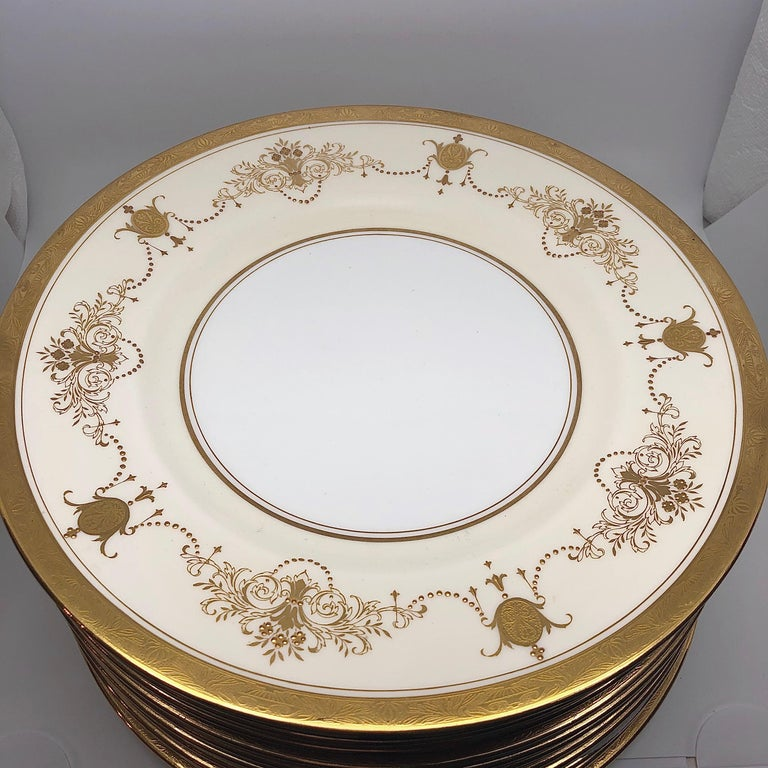 This is a fabulous set of 12 Minton Dinner plates decorated with gilt vases of flowers and ribbons of raised gold jeweling. Minton made them for Davis Collamore in New York in 1911-1920. Davis Collamore was a rival of Tiffany at this time, and sold