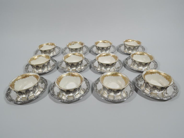 Set of 12 Chrysanthemum sterling silver bouillon bowl holders: Each: Open ring comprising joined stem flowers mounted to underplate with classic rim border comprising alternating flower heads and shaggy leaves. Fully marked including pattern no.