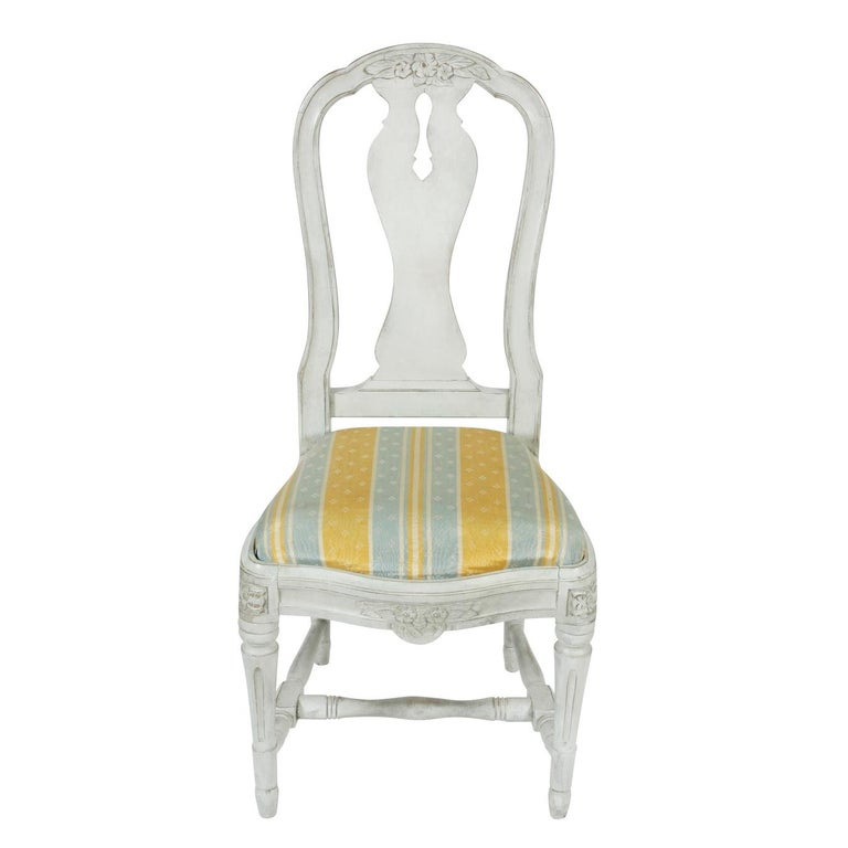 A set of twelve Swedish dining chairs in a soft grayish white finish, with upholstered drop seats, featuring lovely carved detail on the top of backs and on apron, and turned legs. The chairs are comfortable and very well constructed and would look