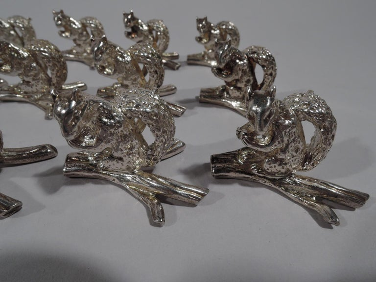 Set of 12 sterling silver place card holders. Retailed by Tiffany & Co. in New York. Each: A squirrel with bushy tail and wary glance grips an acorn with tensile forepaws. An impudent guest for your next dinner party. Squirrel is mounted to a twig