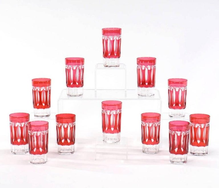 A lovely set of 12 Val St. Lambert crystal tumblers cut to clear in a rare Art Deco pattern. The clean lines with panel cut base are contrasted with the vibrant cranberry overlay. These are very versatile and perfect for any table setting and cold