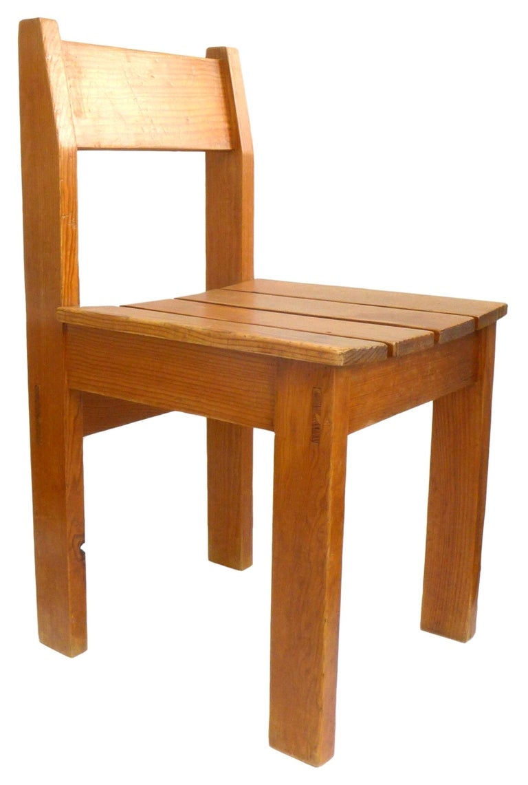 A wonderful set of one dozen European wood slat dining chairs. A well-constructed form with through-mortise details and an attractive profile. Chairs wear an even honey hue with subtle, desirable patina from age. A rare, large set of 12; fantastic,