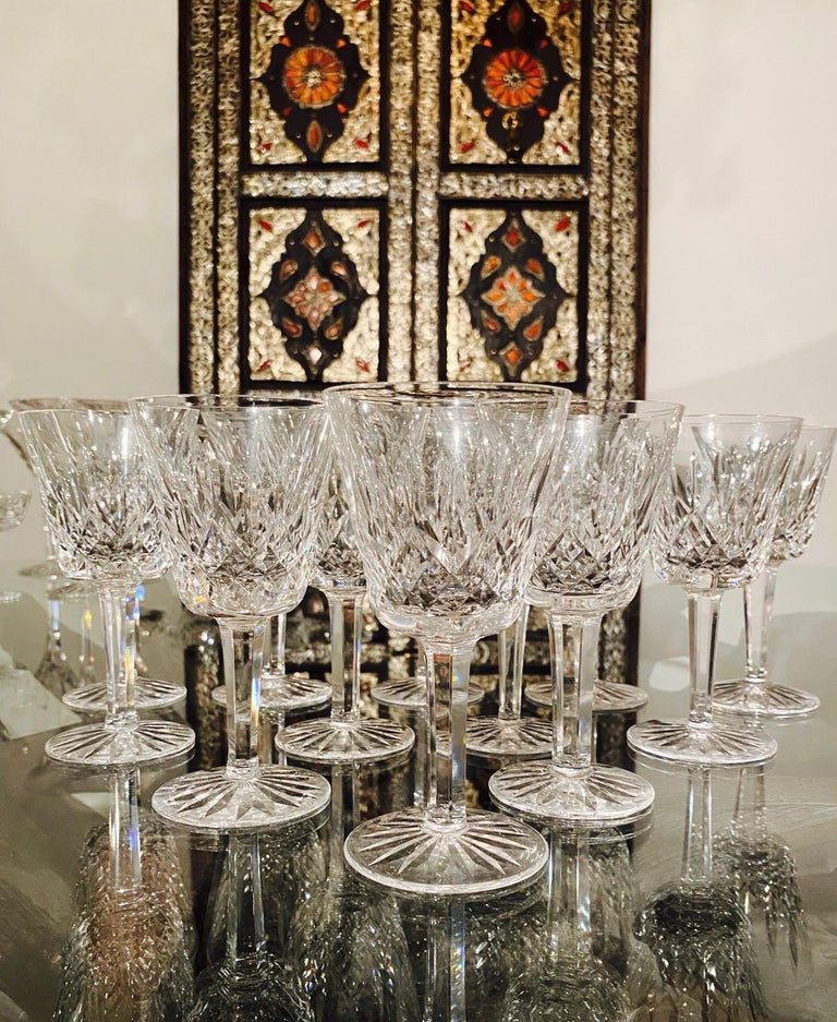 Set of twelve luxury crystal wine glasses from Waterford Crystal. The Lismore Collection is perhaps Waterford's most distinguished design featuring a hand blown crystal with the pattern's signature diamond and wedge cuts. First introduced in the