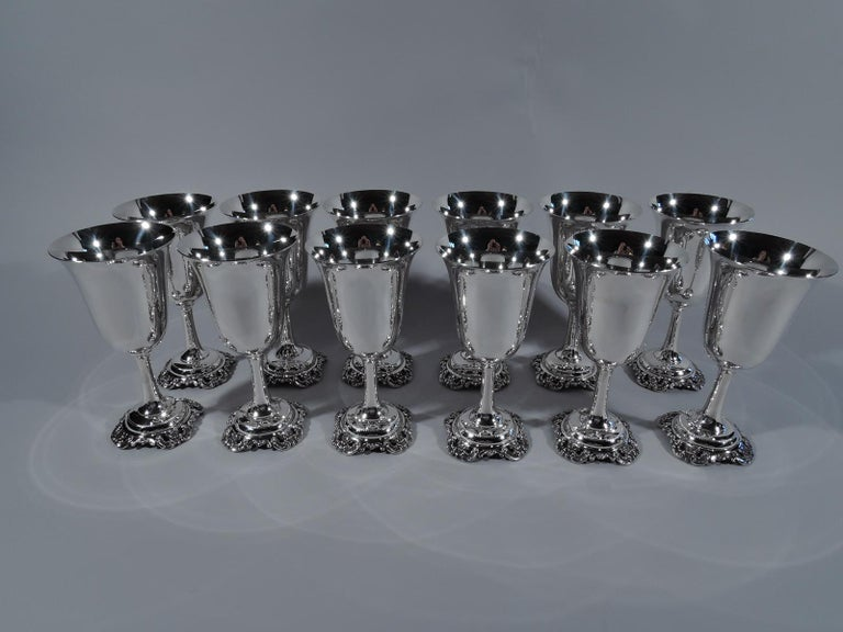 Set of 12 Grande Baroque sterling silver goblets. Made by Wallace in Wallingford, Conn. Each: Bell-form bowl on cylindrical stem on beaded and domed foot applied with open scroll and flower rim. Perfect for a special dinner in the cherished pattern