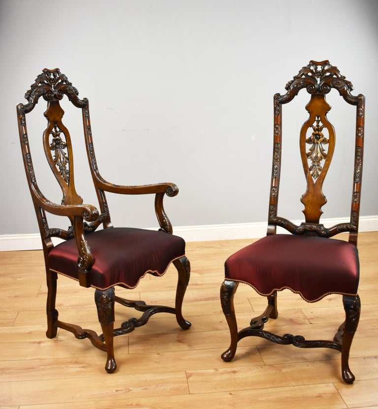 For sale is a good quality set of 14 Queen Anne style dining chairs, each having high backs with carving to the top, standing on elegantly carved cabriole legs united by an ornately shaped and carved stretcher. Each chair is in good condition,
