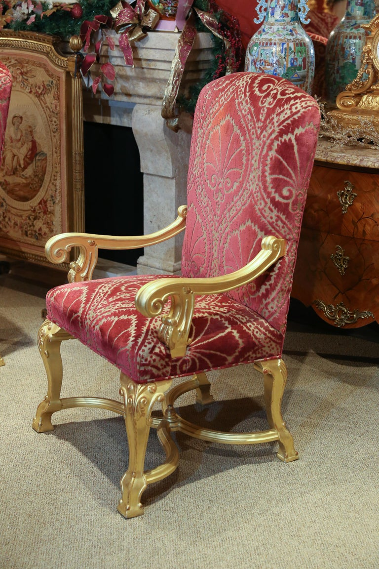 Incredible set of 14 dining chairs in giltwood. Upholstered with Clarence
