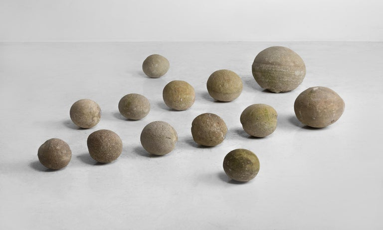 Set of (14) stone balls, France, circa 1840.  Set of cast stone balls of varying sizes with unique patinas.  Measures: 12