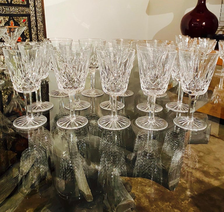 Set of fourteen luxury crystal water goblets from Waterford Crystal. The Lismore Collection is perhaps Waterford's most distinguished design featuring hand blown crystal with the pattern's signature diamond and wedge cuts. First introduced in the