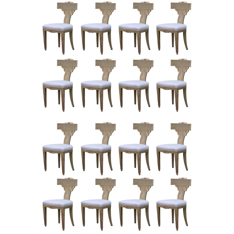 Set of 16 Hollywood Regency painted and carved Klismos dining chairs that we believe may be Italian or Swedish from the 19th century. These have the perfect amount of paint missing and wear. Need to be reupholstered.