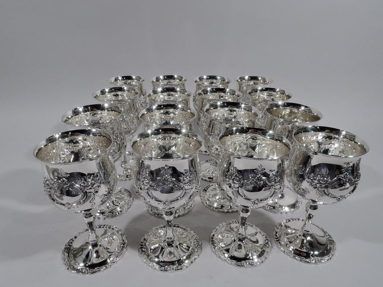 Set of 16 sterling silver goblets in Francis I pattern. Made by Reed & Barton in Taunton, Mass. Bowl has flared rim and rests on baluster stem mounted to raised foot. Strapwork and cornucopia cartouches (vacant) joined by floral garlands. Scrolls
