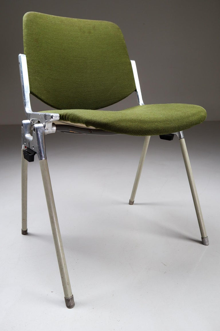 Set of 18 iconic DSC 106 stacking chairs, designed 1965 by Giancarlo Piretti for Castelli. This set features original Italian olive green fabric seats and backs and soft green legs, they are in very nice condition with a signs of wear due to their