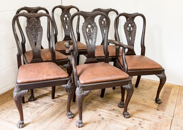A set of carved mahogany and leather dining chairs. Comprising of one carver and five dining chairs. The carver, with wonderful deep carved lion mask details to the arms.  The set is of traditional 18th century style with sweeping cabriole legs