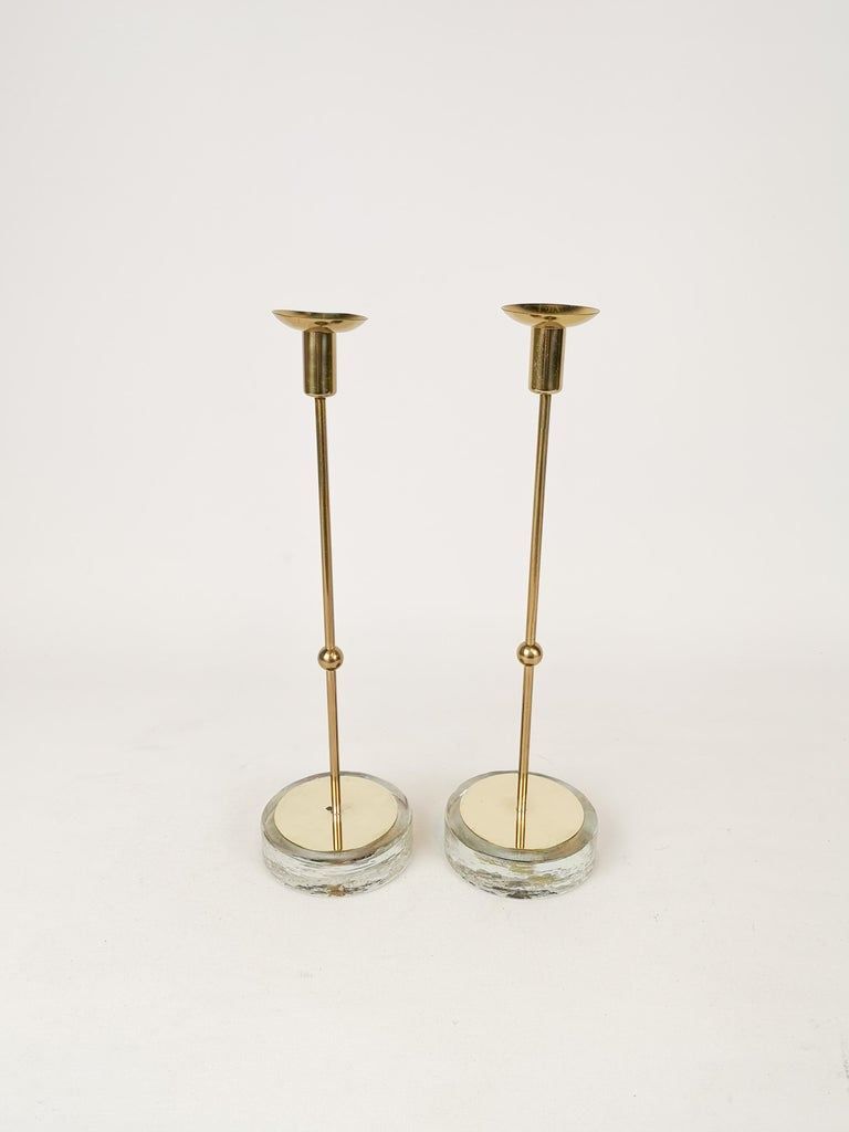 This set of 2 candleholder was designed in Sweden at Ystad Metall and by Gunnar Ander in the 1950s.  The foot is made of glass and the holder in brass.   Good fair condition.   Measures: H 28 cm, D 8 cm.