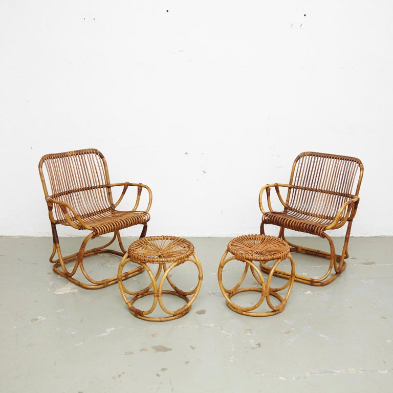Set of two armchairs and two stools desigend by Tito Agnoli. Manufactured by Bonaccina, Italy, circa 1960.  In good original condition with minor wear consistent with age and use.  Materials: Bamboo  Dimensions: Armchair: D 65 cm x W 65 cm