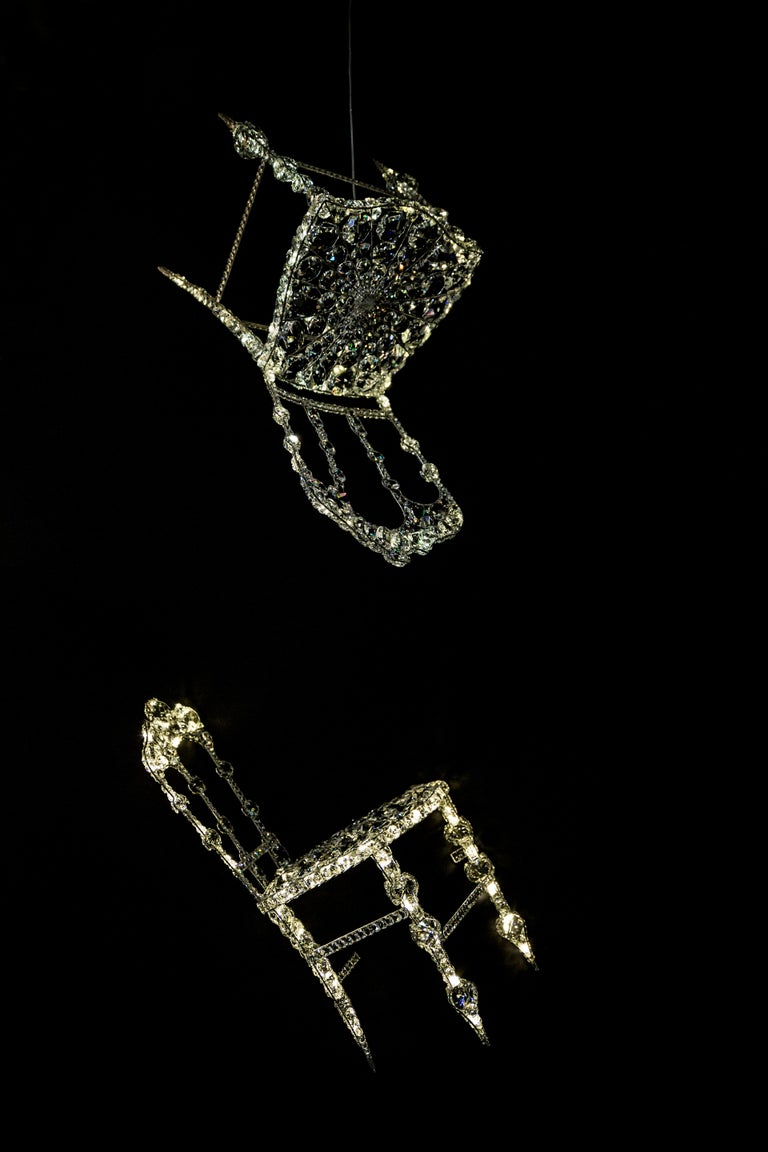 La Chaise suspendue by Geraldine Gonzalez Materials: crystal, Nickel-plated metal, Led Dimensions: H 90 x W approx 45cm Approx 10 kg  Graduated from Duperré School of Applied Arts, Geraldine Gonzalez was a shoe stylist before devoting herself