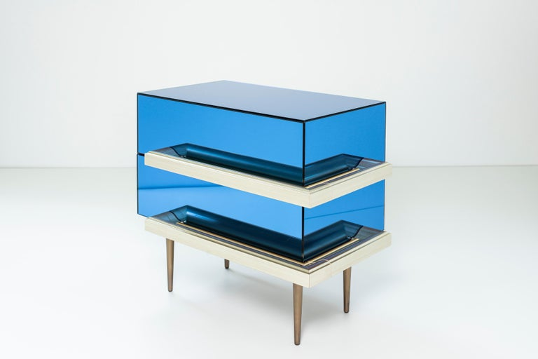 2 drawers mirrored nightstands with finest Champagne picture frame molding handles. Dark walnut finish interior and fade brass metal finish in the legs. Mirror color: Blue.