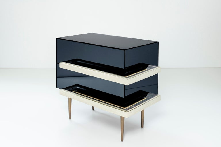 2 drawers mirrored nightstands with finest champagne picture frame molding handles. Dark walnut finish interior and fade brass metal finish in the legs. Mirror color: Graphite.  The traditional French mirror cabinet is reinterpreted leaving the