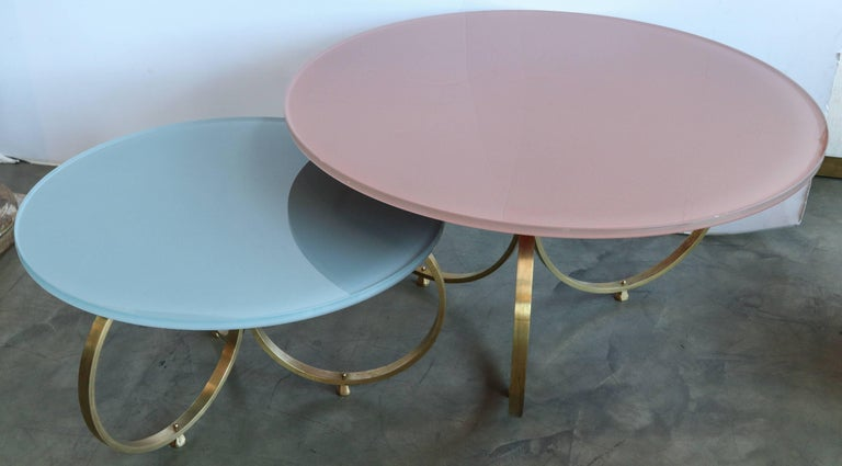 Set of two custom brass coffee tables with reverse painted glass tops in pink and grey. Can be done in any color and multiple metals and finishes  Small: 30in dia x 16.75in high Large: 40in dia x 22in high.