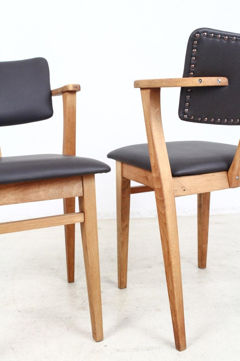 This model Domus armchair was designed by Ilmari Topiovaara and has been completely restored and reupholstered with dark brown faux leather. The scale of the design and the unique design of the arms makes it a great desk chair or occasional chair.