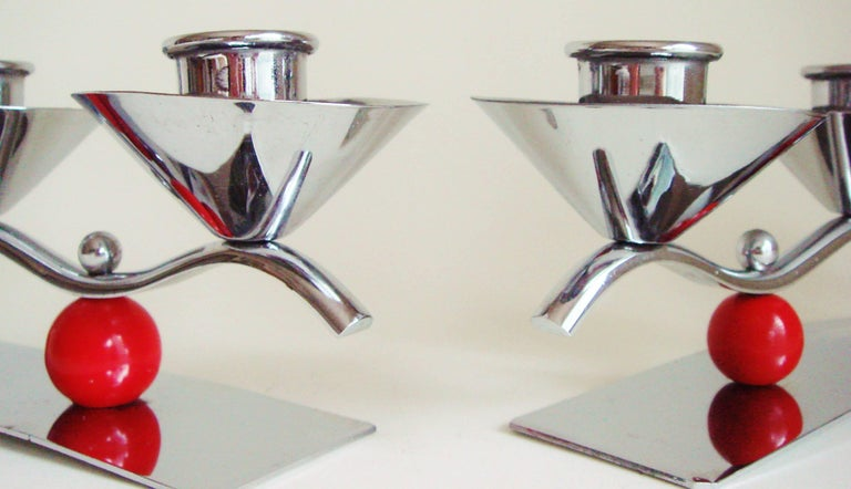These two English midcentury/Art Deco triple candleholders, though almost identical, are not in fact a pair. One dates from just before the war and features a chrome body with two red lacquered wooden spheres while the other is post war and features