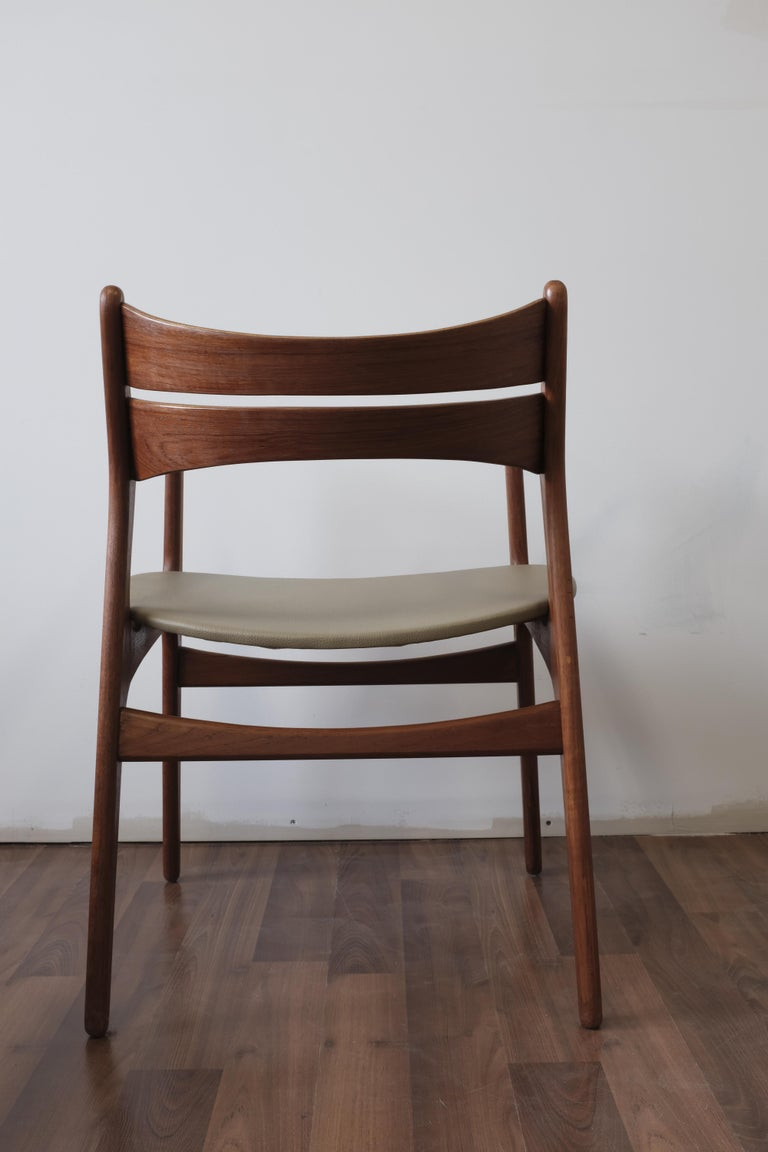 Set of 2 model 310 armchairs designed by Erik Buch and made in Denmark by Christiansen Møbelfabrik.  Frames constructed in solid teak with bent-laminated teak backrests and seats upholstered in a green-beige pebbled leatherette.  4 side chairs