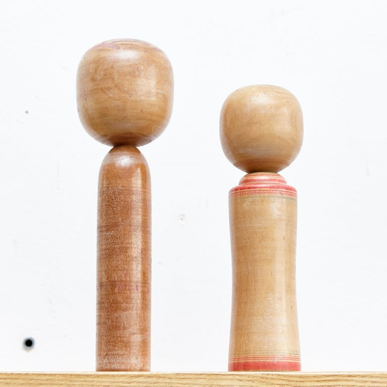Japanese dolls called Kokeshi of the early 20th century. Provenance from the northern Japan. Set of 2.  Measures: 36 x 10 cm 30 x 7.5 cm  Handmade by Japanese Artisants from wood. Have a simple trunk as a body and an enlarged head. One
