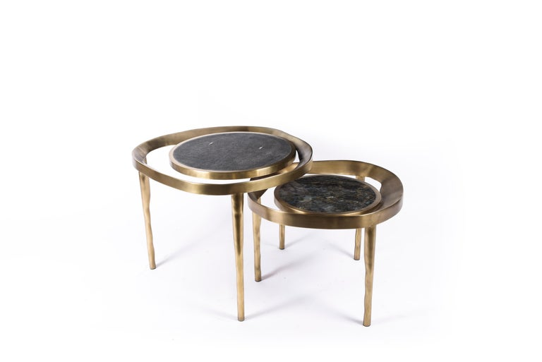 The set of 2 Lily Melting Coffee Tables are a whimsical and dramatic piece for any space. The amorphous-shaped bronze-patina brass frame morphs onto the bumpy shaped legs. The floating circular tops are inlaid in black shagreen and Lemurian stone