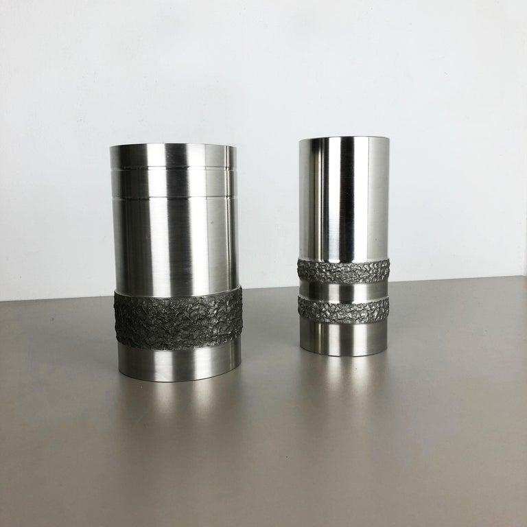 Article:  Brutalist metal steel vases set of 2    Origin:  Germany   Material:  steel metal plastic   Decade:  1970s   Description:  this original vintage vase set, was produced in the 1970s in Germany. it is made of very heavy