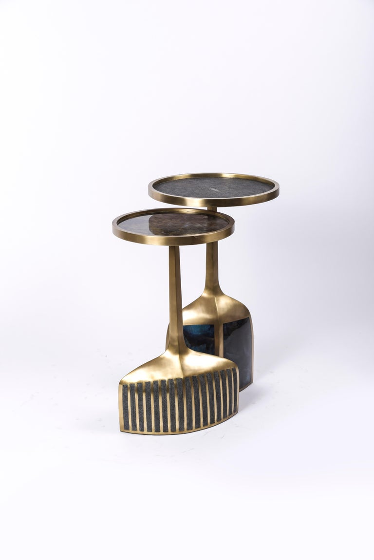 The pedestal side table in small and large are the perfect nesting accent pieces due to their sleek and light aesthetic. The large size is inlaid on the top surface with black shagreen, the bottom part a mixture of blue pen shell and bronze patina