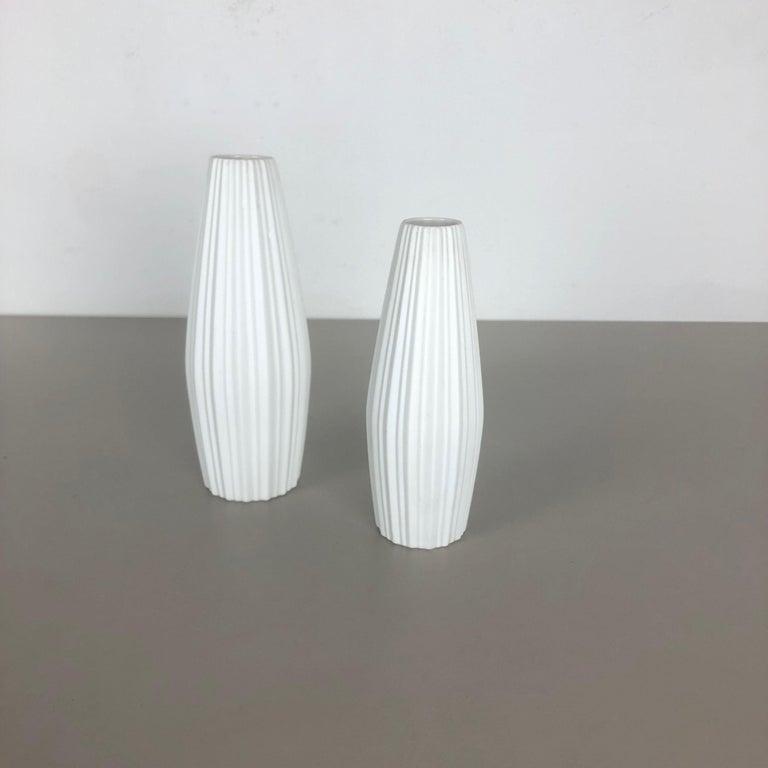 Article:  Op Art porcelain vase set of 2   Producer:  Heinrich Selb Bavaria, Germany   Decade:  1970s    This original vintage Op Art vase was produced in the 1970s in Germany. It is made of porcelain with an Op Art Surface. The