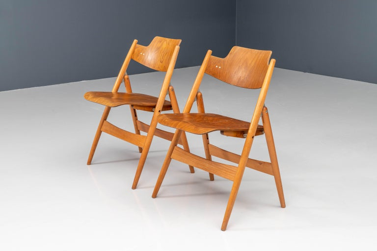 These folding chairs, model SE18, were designed in 1952 by German architect Egon Eiermann for Wilde & Spieth. Its frame is made from beech wood whereas the seat and backrest are made from molded plywood with beech veneer. The chair is now on display