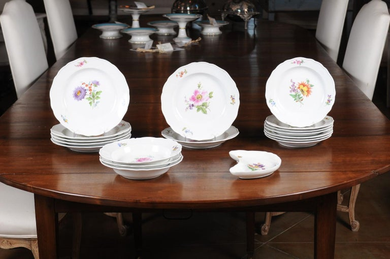 A 24-piece set of German Meissen porcelain service from the 19th century, with floral decor. Born in Eastern Germany during the 19th century, each of this 24 pieces service features a lovely floral décor made of purple, pink, orange or yellow