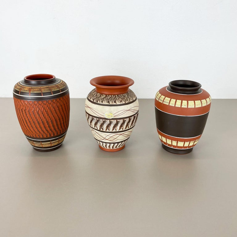 Article:  Pottery ceramic vase set of 3   Producer:  3 different Germany Ceramic Producers    Decade:  1950s    Original vintage 1950s pottery ceramic vase set made in Germany. High quality German production with a nice abstract painting. These vase