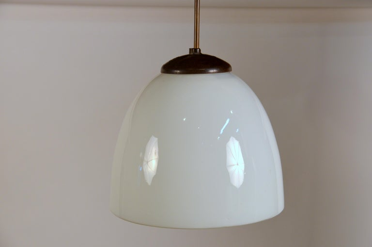 Set of 3 Art Deco opaline glass pendants.  Great over a kitchen center island.  Matching canopy included. The rods are adjustable. The total drop is currently 35 in. from ceiling to bottom rim of the glass globes.  Dimensions listed are for