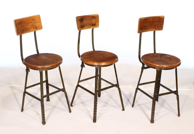Three authentic vintage factory industrial stools. Made from wood and steel. Distressed army green original paint. Seat diameter 15