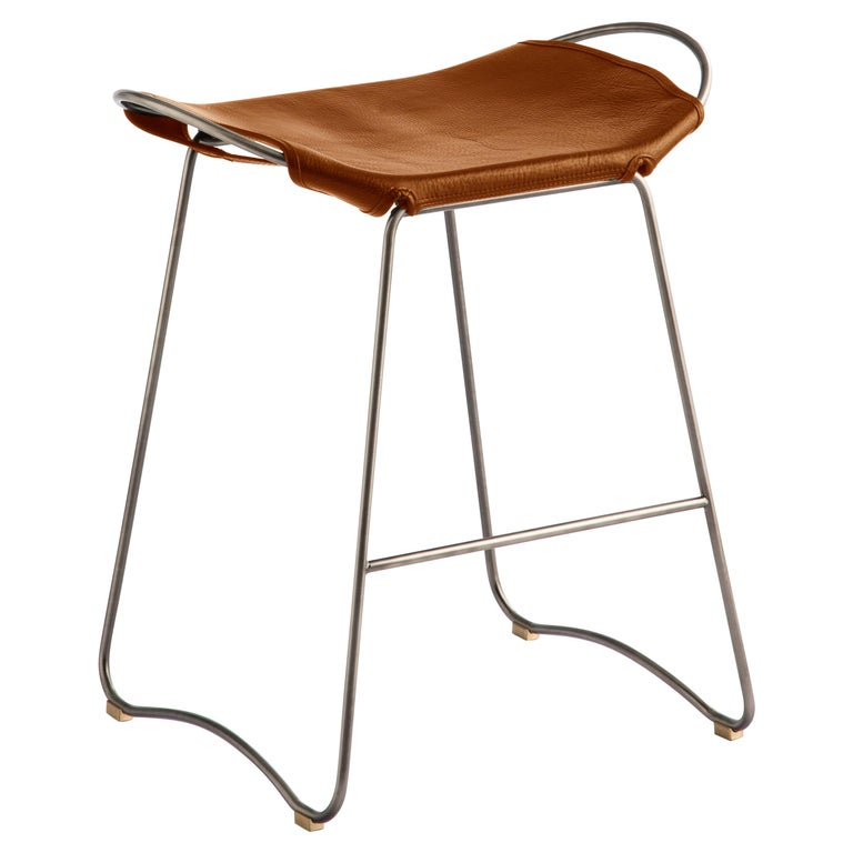 HUG bar stool old silver steel and natural tobacco saddle leather  The Hug bar stool is designed and conceived with a light aesthetic, the slight oscillation of the steel rod of 14 mm is complemented by the flexibility of the 3.5 mm thick