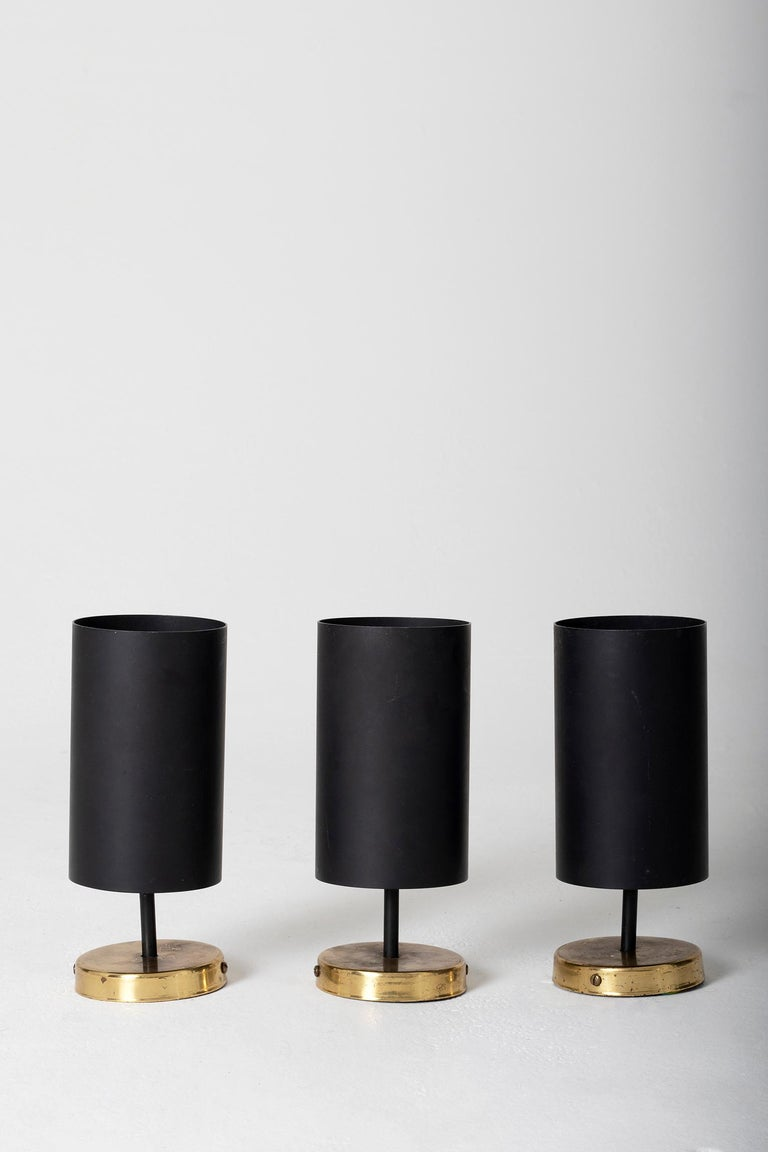 A set of three brass and black enameled iron adjustable spot lights or wall lights, by Parscot Editions, France, circa 1950.