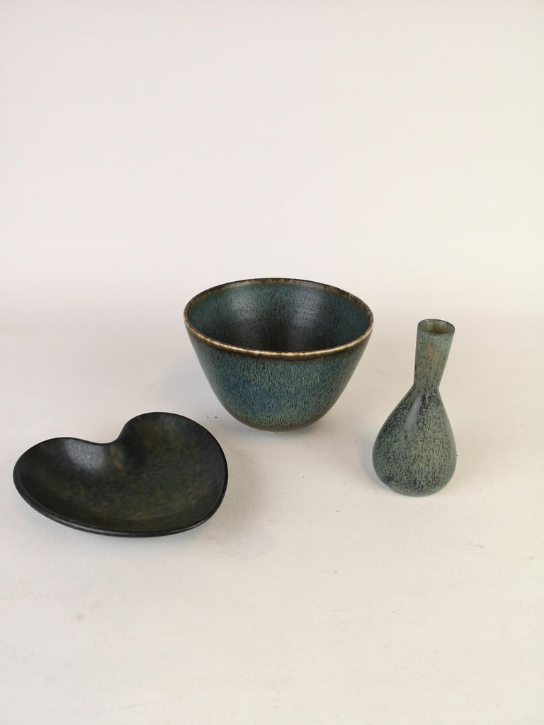 Set of 3 pieces made by Gunnar Nylund and one by Carl-Harry Stålhane. The bowl and the heart shaped bowl are made by Gunnar Nylund and the small vase is made by Stålhane.   Very good condition  Measures. Bowl H 9 cm D 13, small vase H 11 D 6