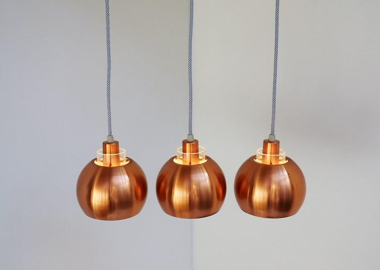 Set of 3 classic copper pendants made in the 1960s most likely by a Danish manufacturer.  The pendants are made in solid copper with white paint inside. At the top there is a transparent acrylic tube in which 3 small brass rods are mounted for