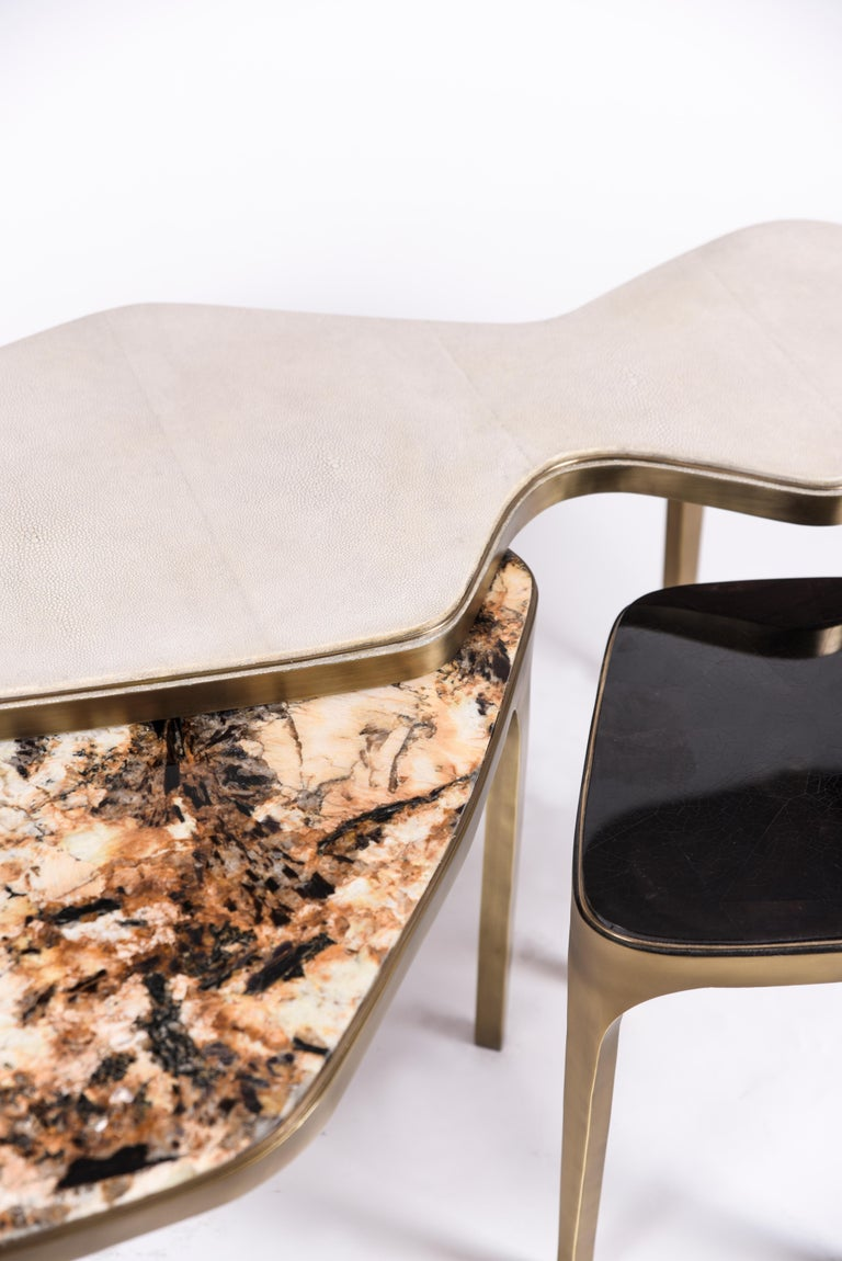 The cosmos nesting coffee tables are both Minimalist and dramatic. The top is inlaid in cream shagreen in the large size, Hwana Stone in the medium size and black pen shell in the small size, that is hand-dyed by artisans, and completed with