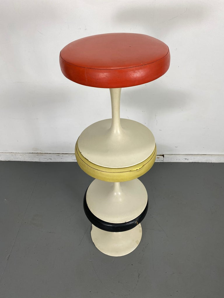 Set of 3 Early Knoll Associates Tulip Saarinen stools.... designed by Eero Saarinen for Knoll Associates, Madison Avenue, NYC. Early bow tie label. Retain Original upholstery., minor paint loss and tear to black stool, minor leather separation to
